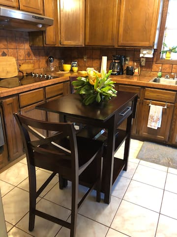 Kitchen island with drop end seating. Coffee pot, with the fixings, cook top, double ovens. Cabinets stocked with dish's, glassware, pots & pans, and even spices.
