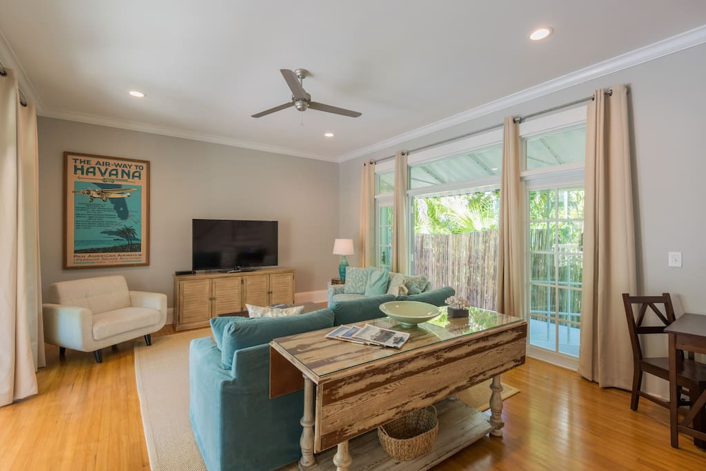 Bright airy and spacious living room with french doors on both sides leading to private patios.