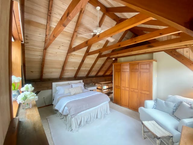 Open floor bedroom with exposed beams and a oversized chair for relaxing.