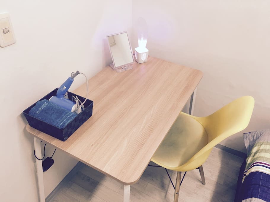 Table with desk lamp, towel, hair drier, mirror and traveler adaptor!