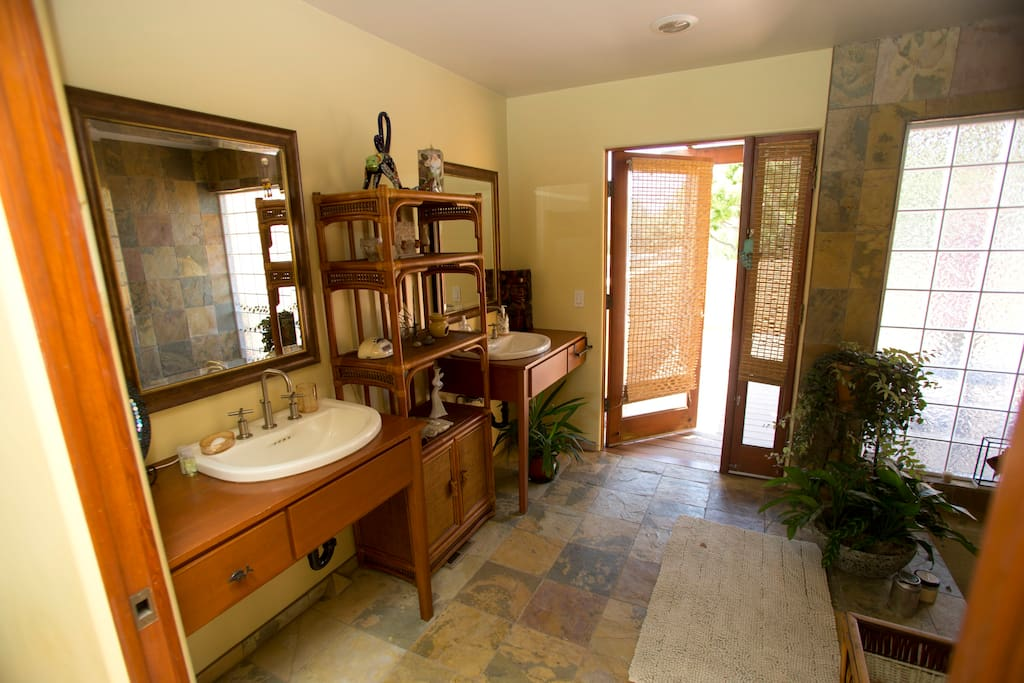Sliding pocket door opens and you are in the bathroom. Two sinks and slate floors.  Door you see is to the deck.a
