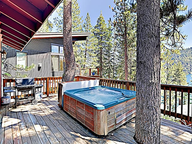 The private hot tub is nestled between towering pine trees.