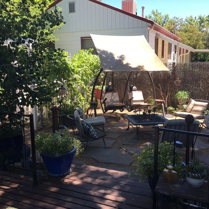 Many guests' favorite:  our two person swing --  individually swinging, with foot rests, adjustable umbrella, and reclining seats -- nestled among the grape vines and garden area.