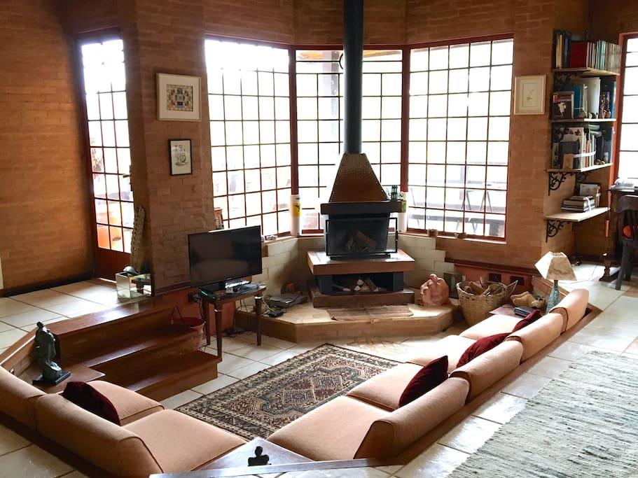 Ampla sala com lareira, perfeita para grupos e rodeada de verde!