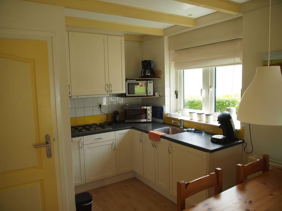 keuken met gasfornuis, koelkast, oven en magnetron
