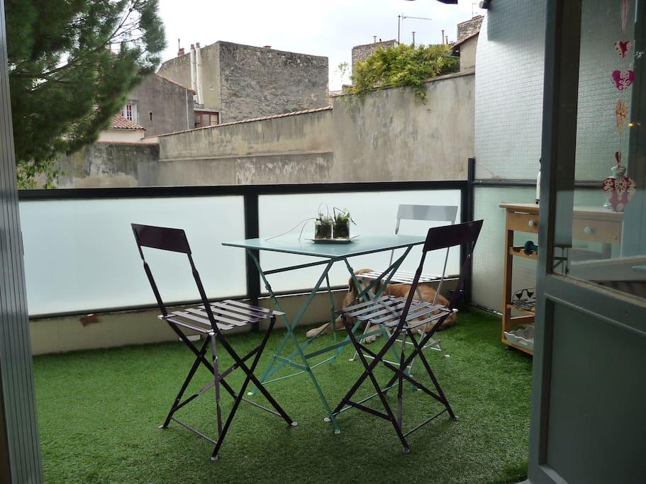 La terrasse est bien agencée avec chaises et tables pour profiter du moindre rayon de soleil
