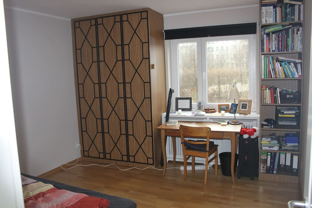 Bedroom with double bed, desk, chair & large wardrobe.