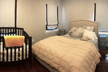 3rd Bedroom with queen bed, crib, blackout shades and private tv.