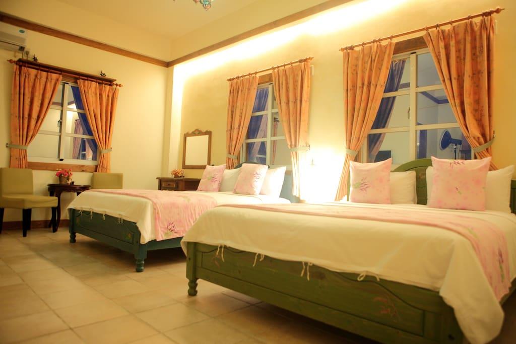 有床架,兩張雙人床。 一旁有梳妝台和桌椅。