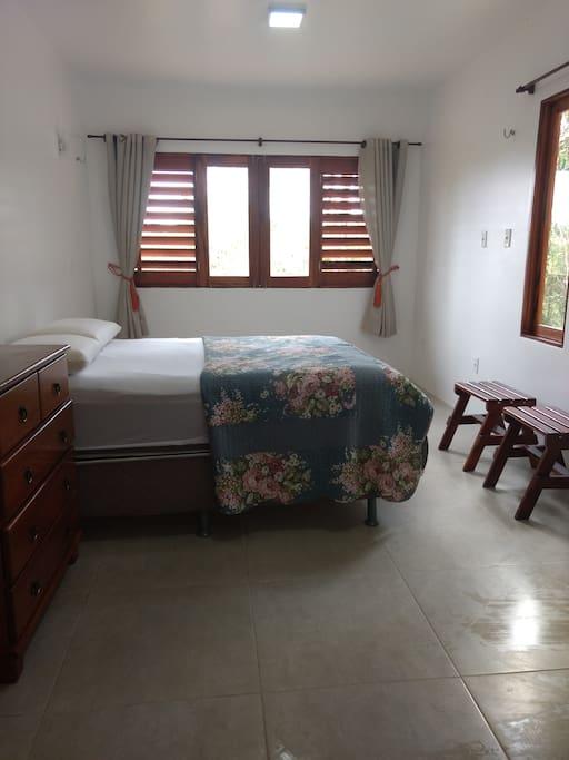 Suite com cama de casal e espaço para duas redes.