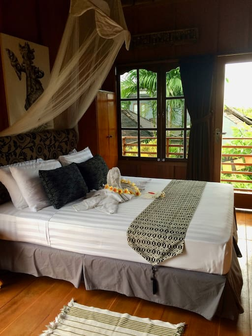 Lumbung suite with wooden floors and walls, enclosed ensuite bathroom and romantic draped net. Has aircon and fan cooling and double bed and views from the veranda.