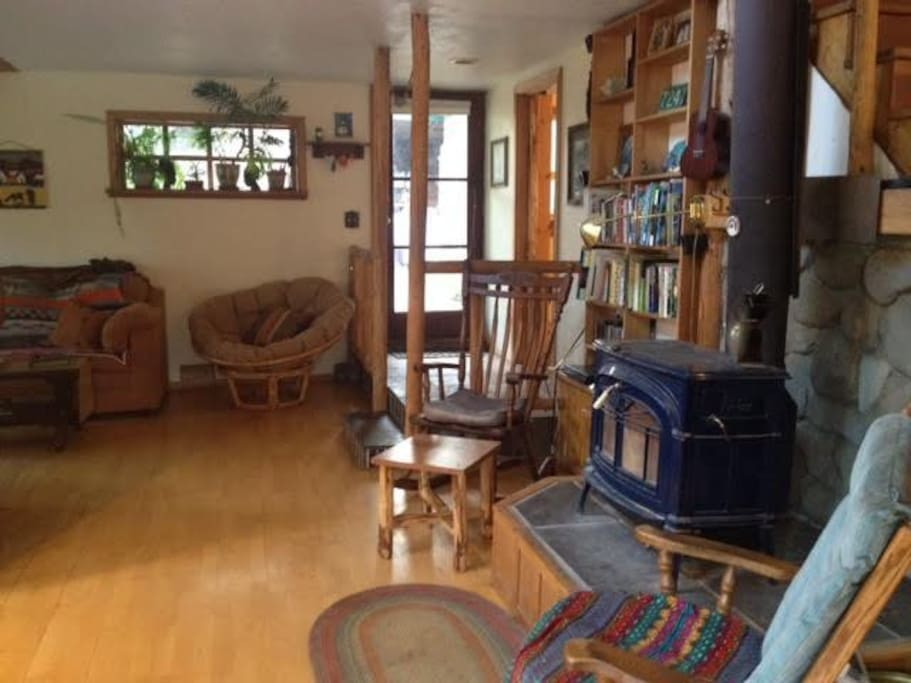 Common area with wood stove, rocking chairs, and couches.