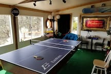 Porch Room Game Room.  Ping pong table works great!  Underneath is a pool table that is weather beaten and old, but still works. Also have a dart board in the room, along with board games and a mini telescope!