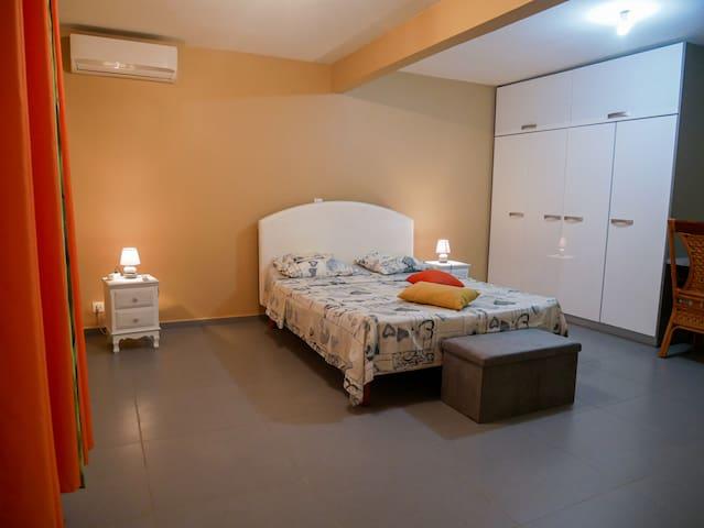 Une chambre climatisée avec un bureau et une grande armoire.
