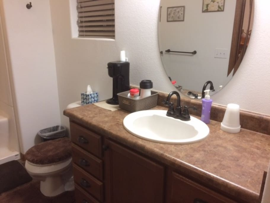 Bathroom counter with K-cup coffee maker, coffee go cups, variety of K-cup coffees, teas, sugar and creamer.