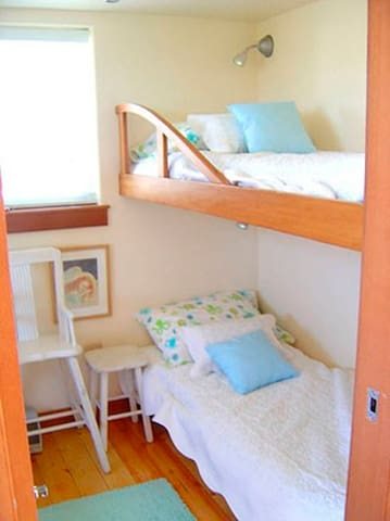 The Library's Bunk Room has TWO Sets of  bunks for four beds, on the right (shown), and two bunks on the left. Lots of big windows create fresh air breezes.
