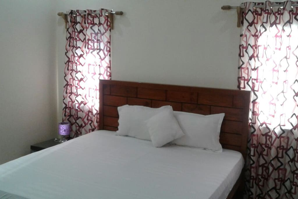 Furnished in vibrant hues of mauve and cream colour, the bedroom has a charming ambience.