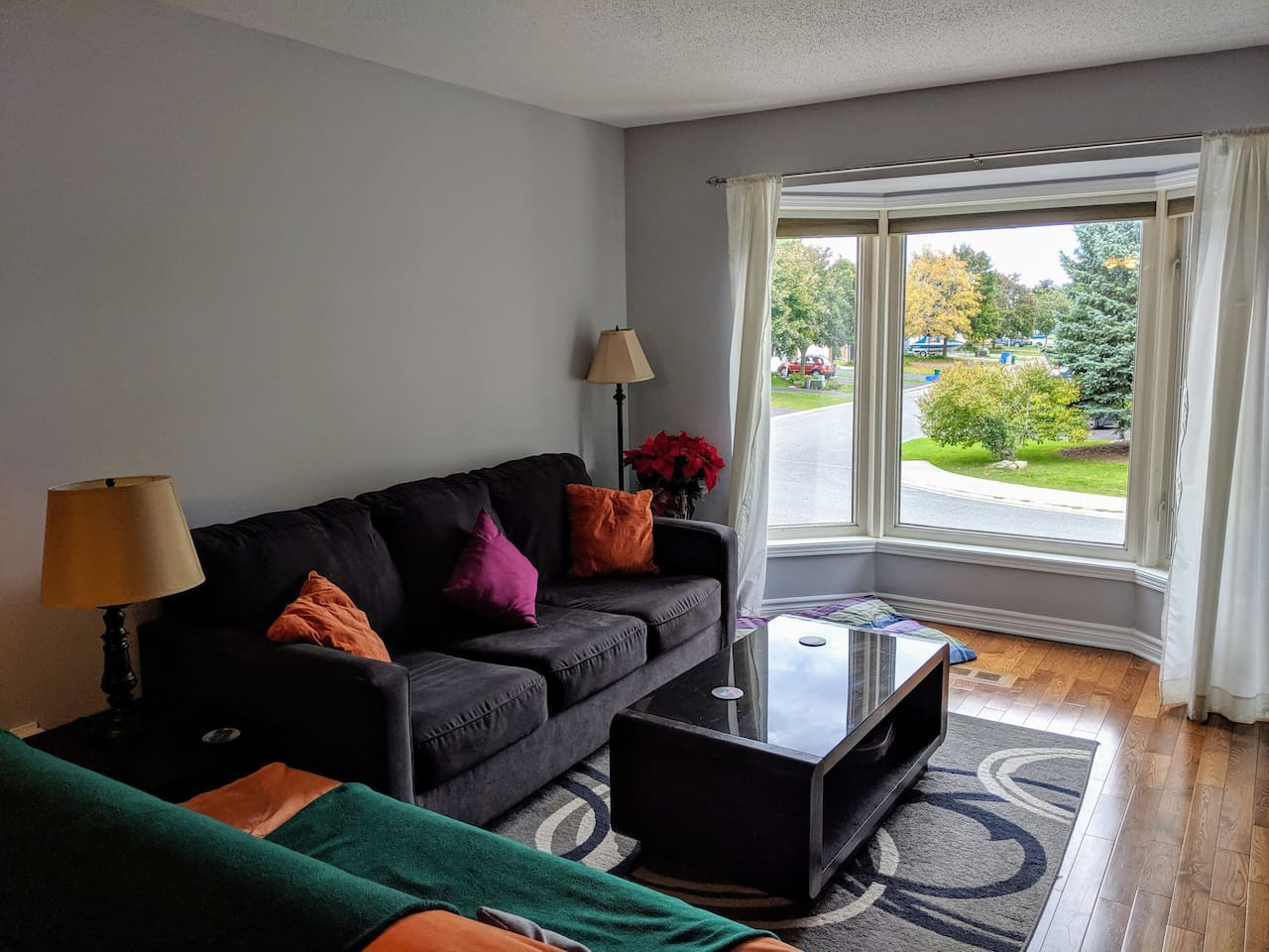 The comfy living room offers a bright bay window, queen-size sofa bed and futon (seating only).