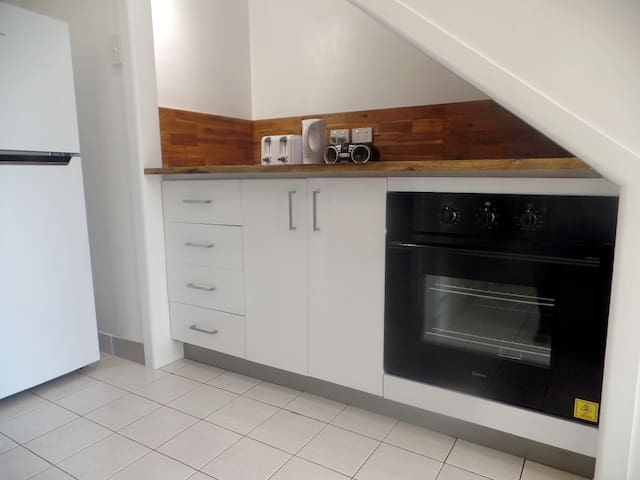 Granny Flat Kitchen showing Wall Oven, Fridge, Toaster and Kettle.