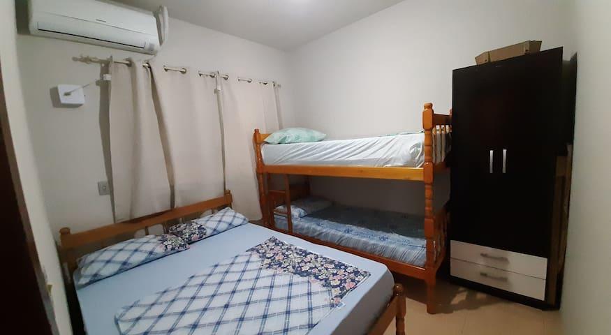 Quarto com cama de casal e beliche, tem lençóis na cama e fronha no travesseiro, ar condicionado