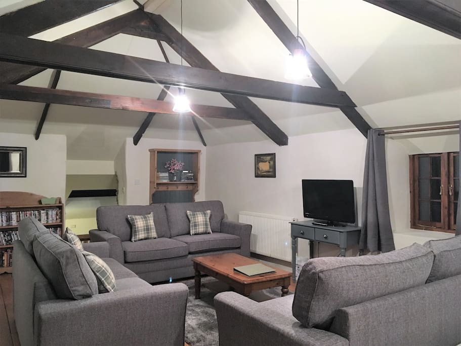 Another view of the spacious lounge with vaulted ceiling and exposed beams.  This room is bathed in natural light from two velux skylights and also has a large window and (very!) small door overlooking the back garden