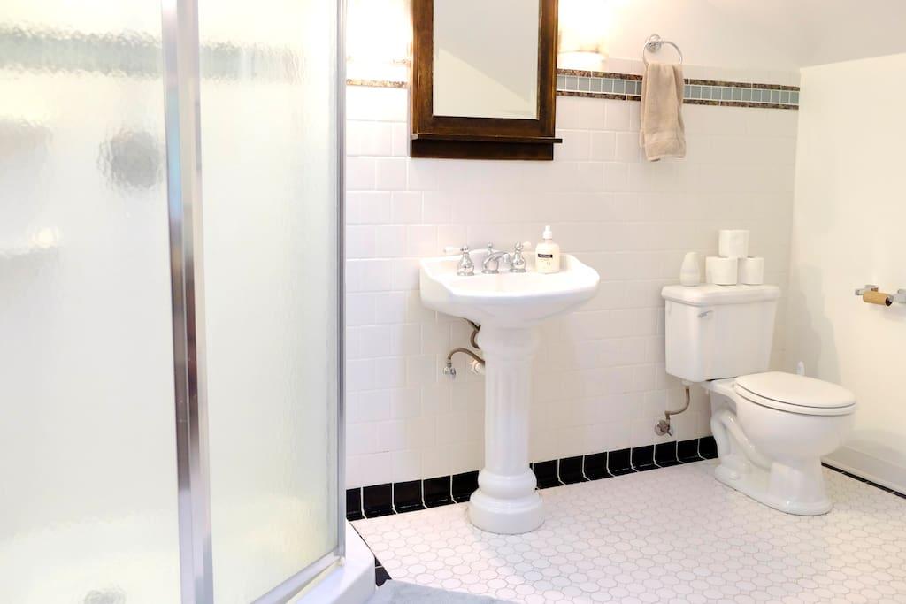 Clean fresh white tiled bathroom and shower
