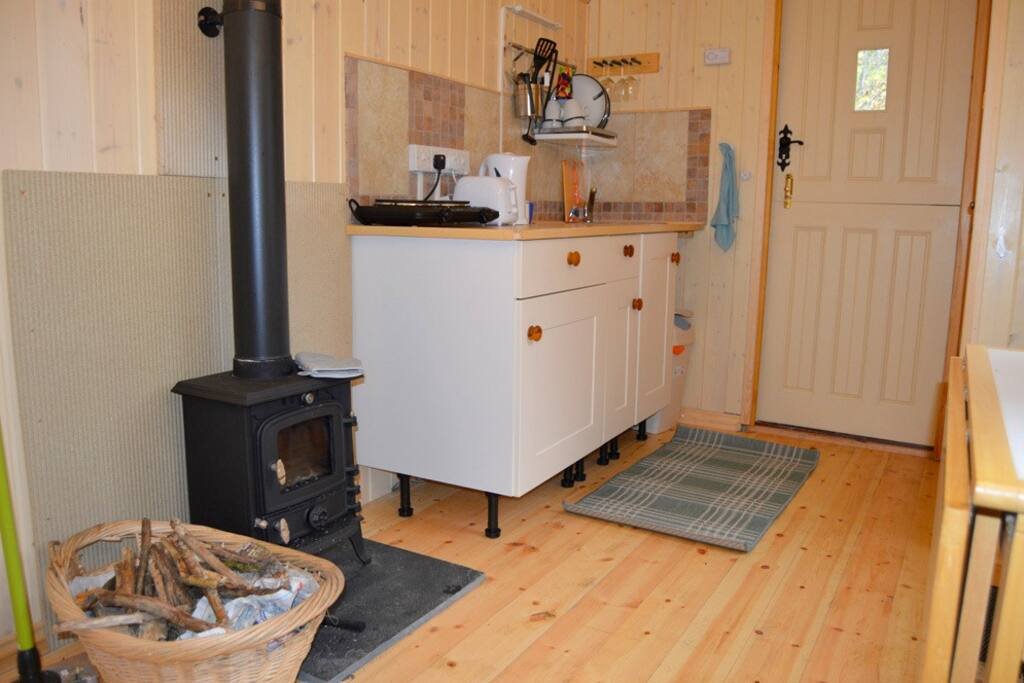 Kitchen area , log burner and door to bathroom