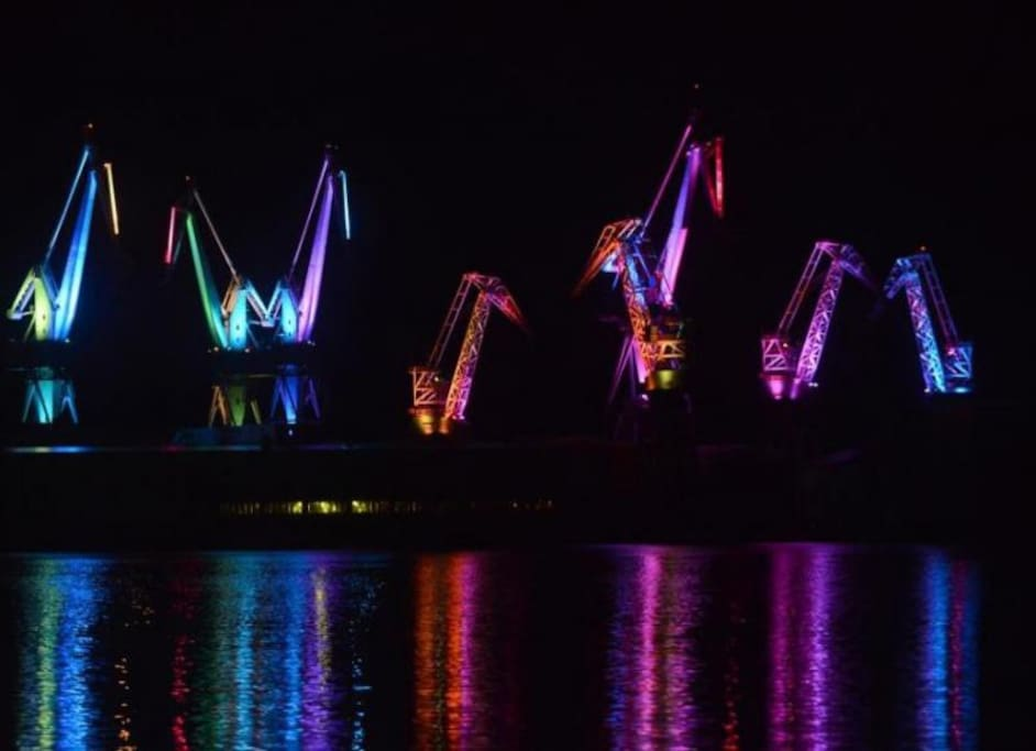 Lighting giants,shipyard;s cranes that are lightened up during the night
