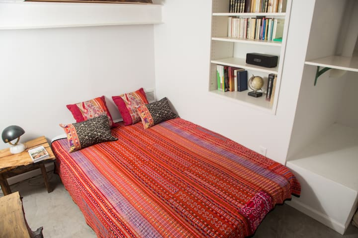 Second bedroom with full-size bed, beautiful vintage window and little desk area. Live edge tables. Ethnic blankets and pillows. Nice closet space, with shelve, coat rack, and luggage table. Individual AC unit and fan. Many Extra blankets/bedsheets.