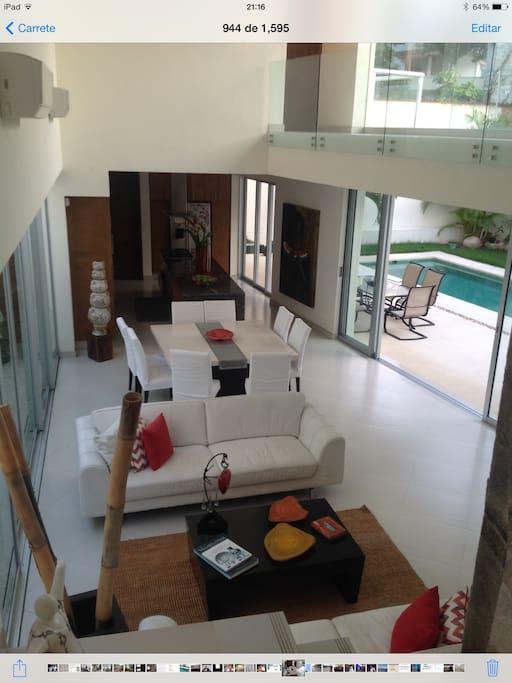 Vista de  áreas comunes, sala, comedor, terraza y alberca