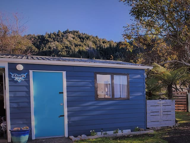 The outside of The Lake Room. A big ranch slider door is around to the right giving separate entry to the garage. This space offers great outdoor living, lake views, table & couch as well as a super comfy single bed. Dining/work table and chairs.
