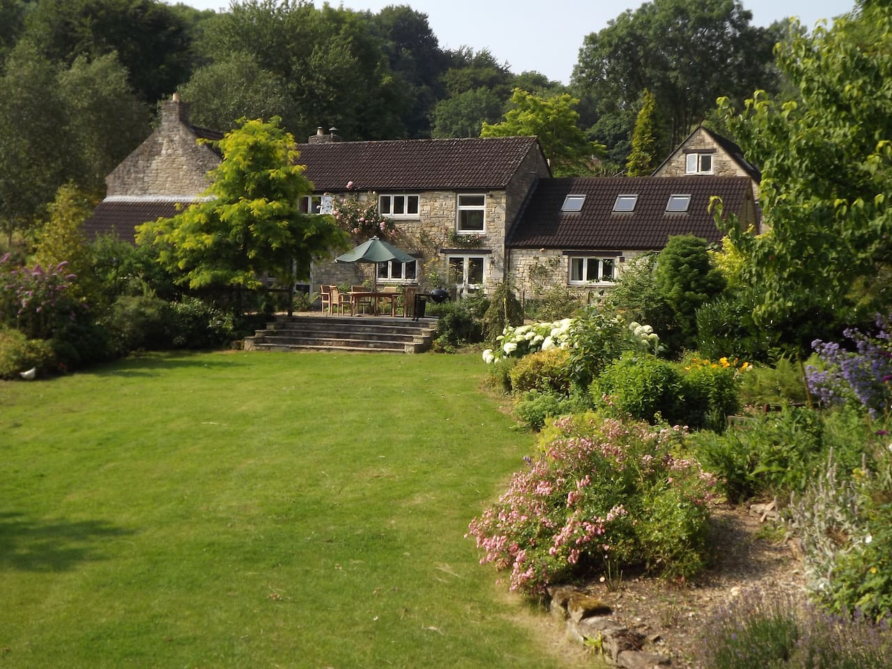 The picturesque riverside lawn at River House Bath  can be set up with garden games, such as croquet, badminton and clock golf. There are sun loungers on the paved terrace directly beside the river, a separate BBQ terrace (shown) and private fishing