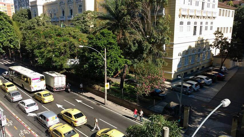 Visão panorâmica da rua em frente ao apartamento com a ciclovia, táxis e ônibus na porta
