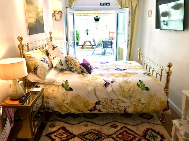 King size quality metal framed bed, view shows french doors leading onto decked courtyard garden. Smart TV in both bedrooms. Beautiful bedding in both bedrooms