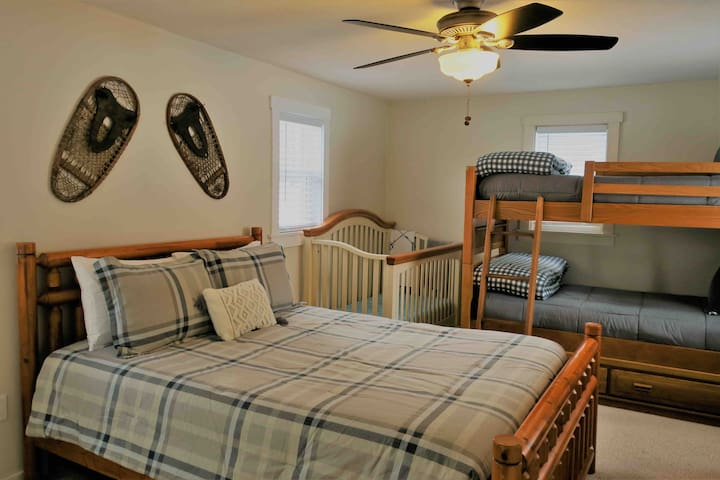 Master bedroom off of family room. Queen size bed, twin bunk beds and crib.