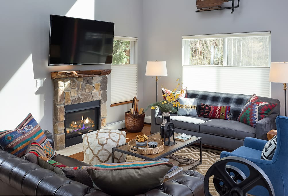 Bright and welcoming living room with a toasty gas fireplace. Complimentary Wi-Fi is provided.