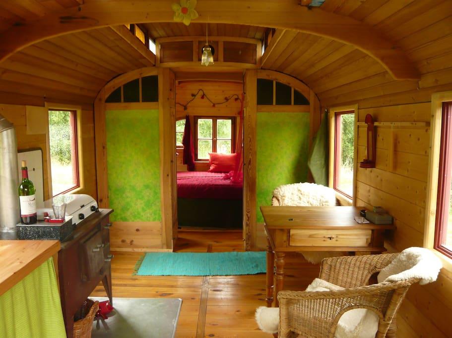 Wohnzimmer mit Kuschelecke im Hintergrund. Für kalte Tage gibt es einen Holzofen, der schnell eine gemütlicheAtmos-phäre schafft.