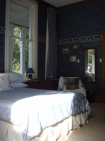Queen-sized bed and single bed in a sunny, warm room.