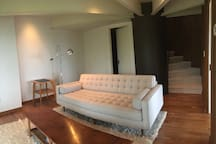 Guest sitting room designed for lounging with comfy long couch and table/bench for resting one's feet or coffee upon!