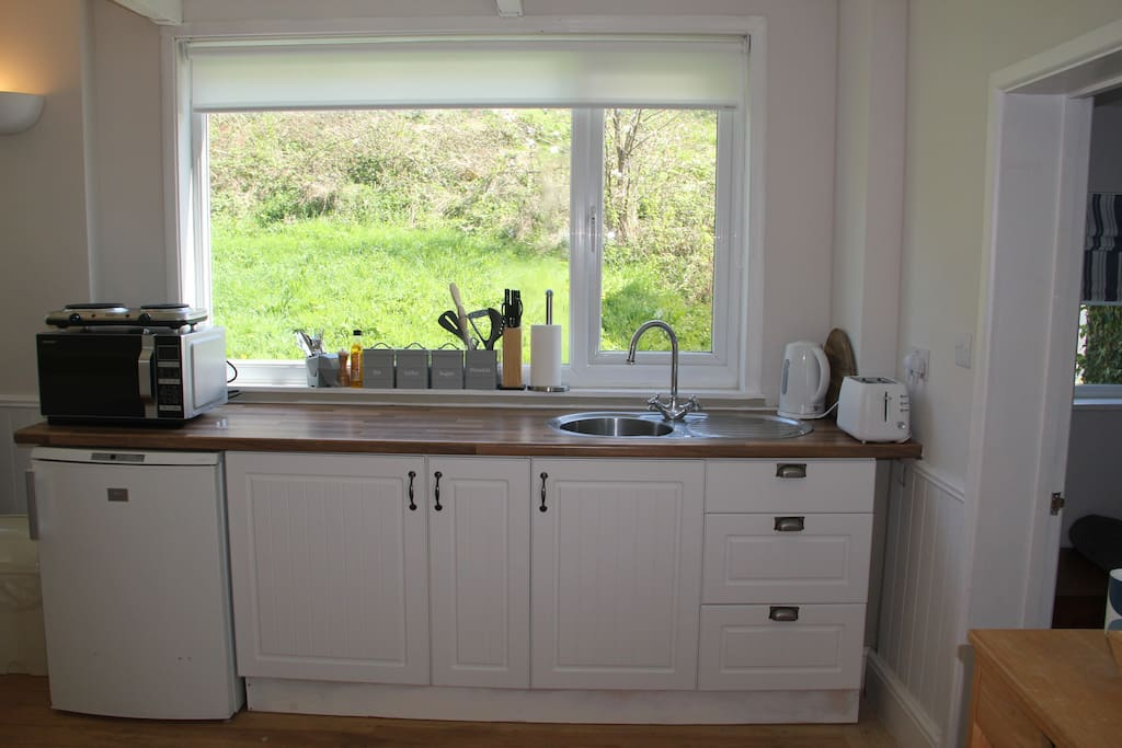 Kitchen area equipped with all the essentials. Combi microwave oven, fridge, kettle, toaster, ceramic hob plus all the utensils and crockery you need. Tea, coffee, sugar and milk are provided.