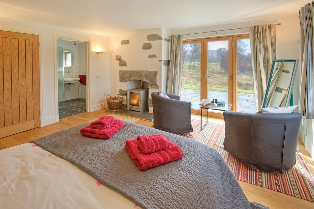 Bedroom with king-size bed, walk-in wardrobe, TV and en-suite shower room.