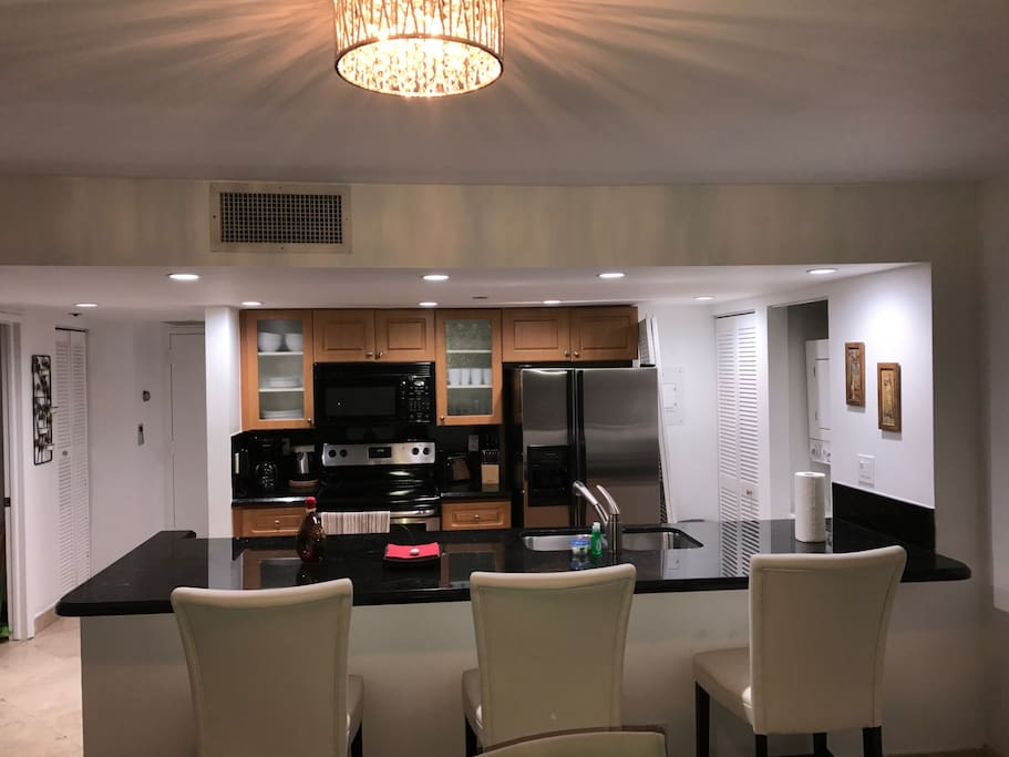 Kitchen with 3 white bar stools