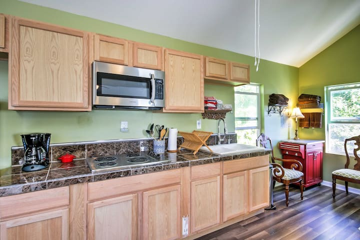 The kitchen is well-equipped with a microwave, cooktop, and full-sized refrigerator.