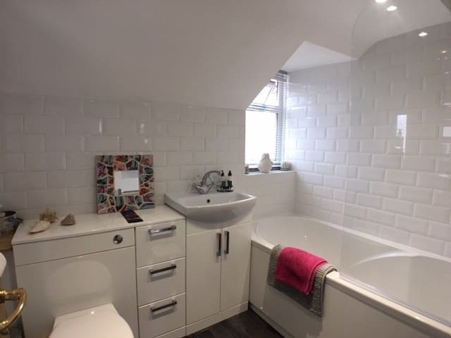 Private bathroom with overhead shower in the bath.