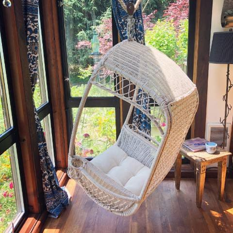 A hanging rattan chair gives a view into our flower gardens and beyond.  Watch the hummingbirds feed or relax with a book and a cup of tea.