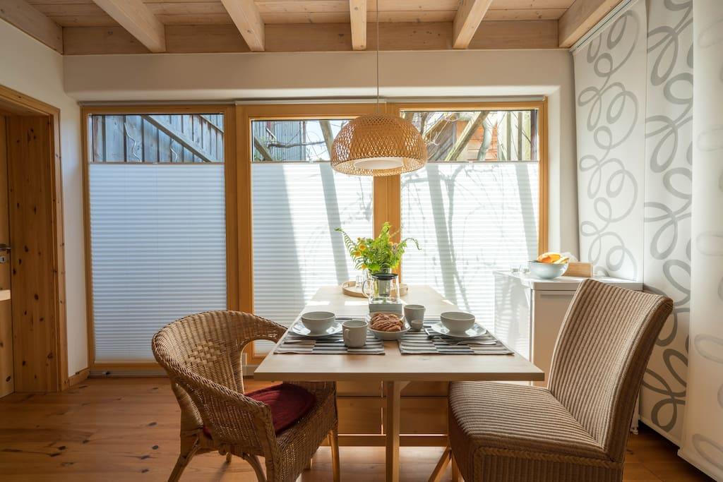 Durch die Schiebetür in der Mitte der Fensterfront kommst du auf eine kleine Frühstücksterrasse.