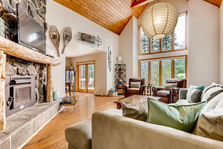 """The gorgeous """"Great Room"""" has high vaulted tongue and groove ceilings, a wood-burning fireplace and awesome floor-to-ceiling windows."""
