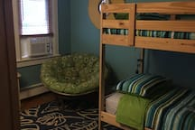 Bunkbeds work great for this small but ample bedroom. Wicker desk, amoire, comfy chair, ceiling fan and air conditioner are all right next to main bathroom.
