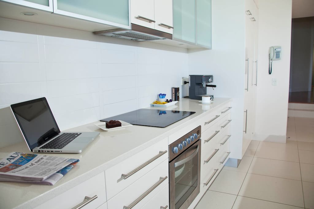 The kitchen is sleek, spacious, and well equipped.