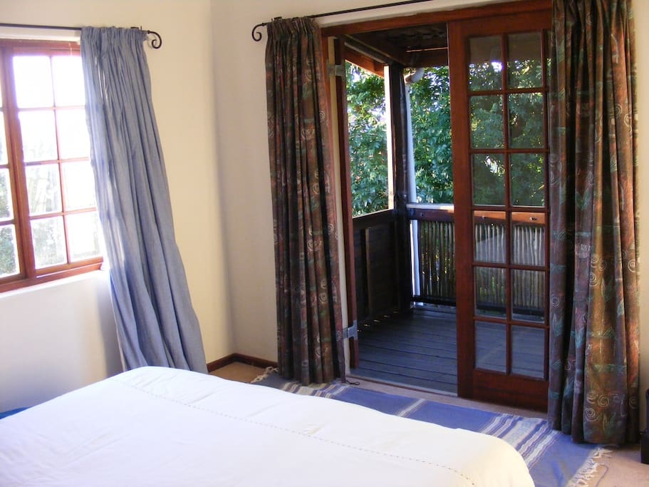 The Master Bedroom has a queen sized bed and a door that opens up onto a large balcony.